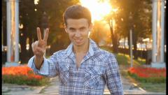 Victory sign by sexy man in blue shirt, sunny park, click for HD Stock Footage