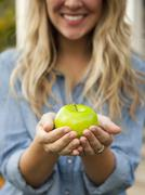 Stock Photo of Mid-section of young woman holding green apple