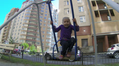 Small girl swinging on a swing on playground in yard Stock Footage