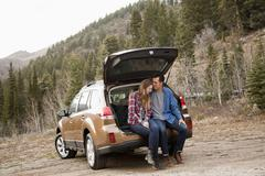 Portrait of young couple sitting in car trunk in non-urban scene Stock Photos