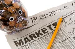 investments opportunity - newspapers open to business related pages with pigg - stock photo