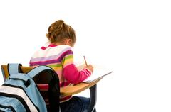 Young girl doing school work at desk Stock Photos