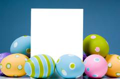 brightly colored easter eggs surrounding white, blank notecard - stock photo