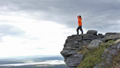 Girl in the mountains, comes to the edge of the cliff and looking ahead Stock Footage