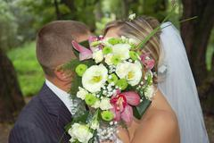 groom and fiancee kiss after a bouquet - stock photo