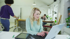 Happy young students working together with technology in a shared study space Stock Footage