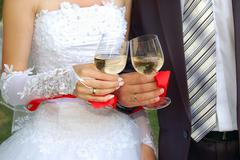 glasses with champagne in the hands of groom and fiancee - stock photo