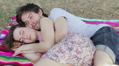 Tenderness, two lovers embraced on the lawn exchange kisses and laugh Stock Footage