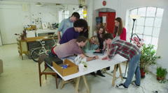 Diverse group of young students working together on a project  Stock Footage