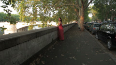 Sad and pensive girl with red dress at sunset - steadycam Stock Footage