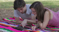 Tablet - Happy young couple with tablet computer in the park - watching photo Footage