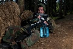 Paintball player resting on the ground Stock Photos