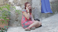 Stock Video Footage of beautiful smiling young woman is talking on cellphone sitting in ground