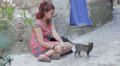sad and lonely young woman sitting on the street stroking a kitten HD Footage