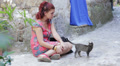 sad and lonely young woman sitting on the street stroking a kitten Footage