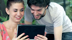 Young man and woman having fun using webcam of a tablet computer Stock Footage