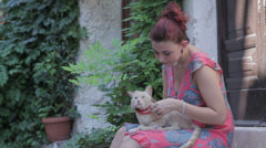 Beautiful young woman playing and stroking ( pet ) a cat Stock Footage