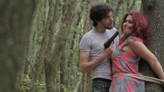 Woman tied to a tree is tortured by a maniac psychopath criminal - fear Stock Footage