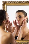Stock Photo of cute brunette at mirror