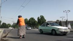 Poor lady sweeping the road in Dushanbe Stock Footage