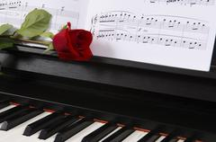 sheet music with rose on piano - stock photo