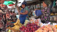 Fruit stall in Tajikistan, ladies with headscarves, colorful dresses Stock Footage