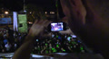 boy takes pictures of a crowd in an outdoor disco Footage