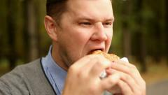 Young businessman eating a hamburger Stock Footage