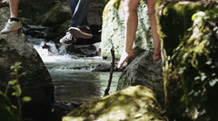 Live in contact with the nature - legs dangling from a tree near a stream Stock Footage