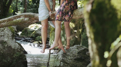 live in harmony with the nature - legs dangling from a tree near a stream - stock footage