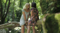 Two girl friends are laughing and talking and  they are sitting on the tree HD Footage