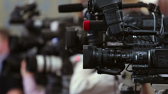 Operators work with equipment in row of few cameras Stock Footage