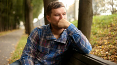 Depressed, sad young man sitting in the park, 1080p - stock footage