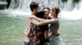 girls of boys have fun in a waterfall. hugging and playing with water Footage