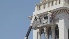 Masons do maintenance work of a church with a boom lift - crane - worker Stock Footage