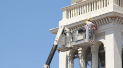 Bricklayer  do maintenance work of a church with a boom lift - crane - worker Stock Footage