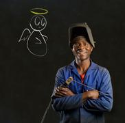 African black man industrial worker with chalk angel on blackboard background Stock Photos