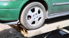 Car stands on lifting machine at outdoor service Stock Footage