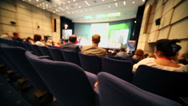 Stock Video Footage of People sit on rows of chairs in auditorium during conference