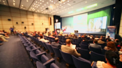 People sit on rows of chairs in large hall during conference - stock footage