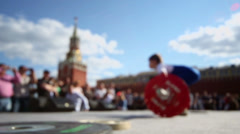 Crowd watch young boy which lifts barbell near Kremlin in Moscow Stock Footage