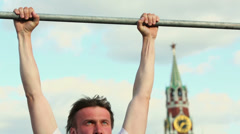 Young man does chin-ups near Kremlin Tower against sky Stock Footage