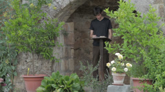 A poet reads a book placed on a bookrest in a beautiful  garden - poetry -  man Stock Footage