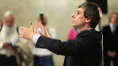 Man conducts by Academic big chorus of RSUH at metro stations - stock footage