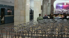 People sit on chairs and look at choir which sings in metro Stock Footage