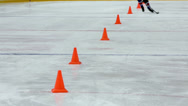 Stock Video Footage of Hockey player with stick moves puck and rides around cones