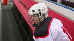 Hockey player sit on bench and drink water from bottle Stock Footage