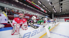 Several hockey goalkeepers watch on ice from bench Stock Footage