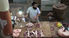 Muslim man cleaning meat at Central Asian bazaar Stock Footage