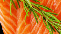 Fresh raw salmon fillet on black with rosemary Stock Footage